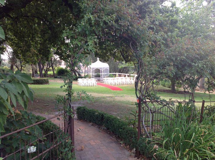Wedding ceremony setup at the gazebo shot through the garden archway
