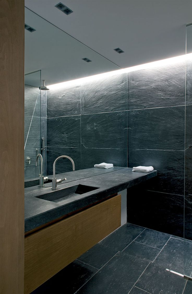 Bathroom Mirror Ideas - Fill The Whole Wall | This full wall mirror starts at the level of the vanity and continues all the way up to the ceiling of this stone tile clad bathroom.