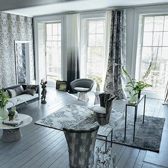 A statement modern graphic Designers Guild rug in luxurious and lustrous hand knotted bamboo silk. The vintage graphite damask motif sets beautifully against softly shading greys.