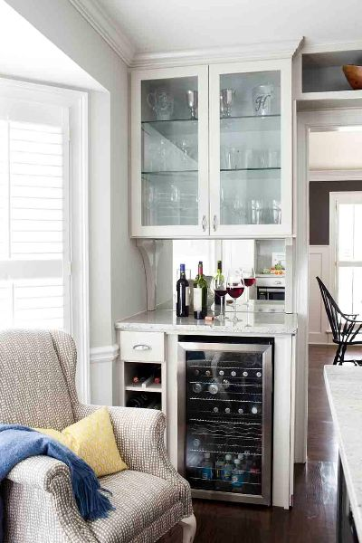 terracotta properties kitchen features lounge area with patterned gray wingback chair and yellow pillow diy bar with mini fridge - Glass Front Mini Fridge