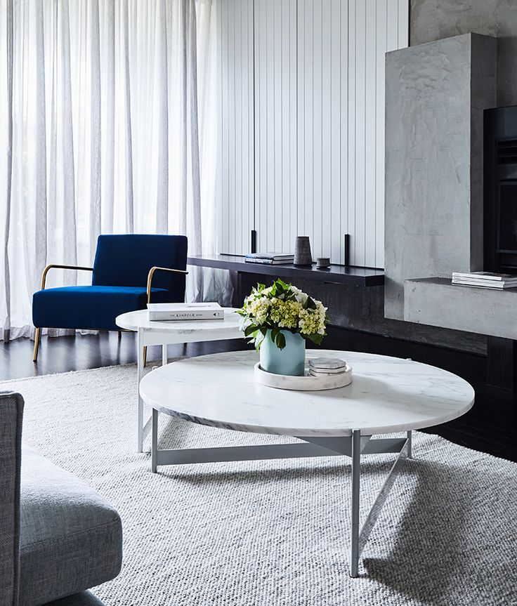 White marble round nesting coffee tables, light grey rug, sheer pale grey curtains, dark floorboards, blue armchair with gold frame