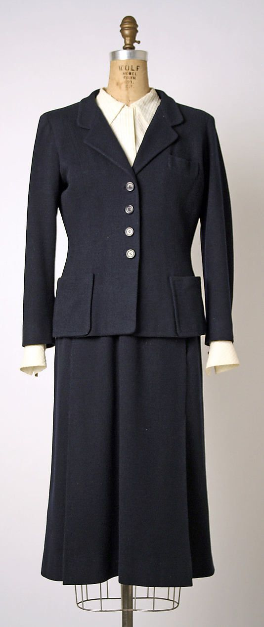 This suit is by Coco Chanel for spring/summer 1954. Chanel reopened her house after retirement upon the popularity of the New Look. Her 1950s looks were classic Chanel with cardigan suits and tailored shapes.