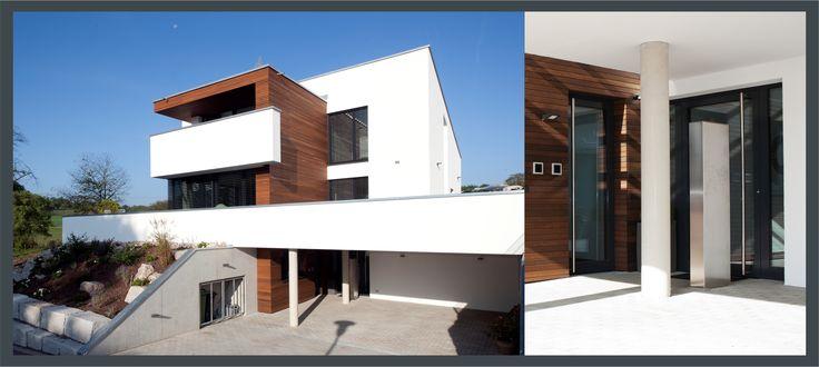 Hanghaus in modernem Design. Die in den Baukörper gezogene Eingangsebene befindet sich auf Straßenniveau, Haustüren aus Glas sorgen für eine gute Belichtung im Hausinneren.