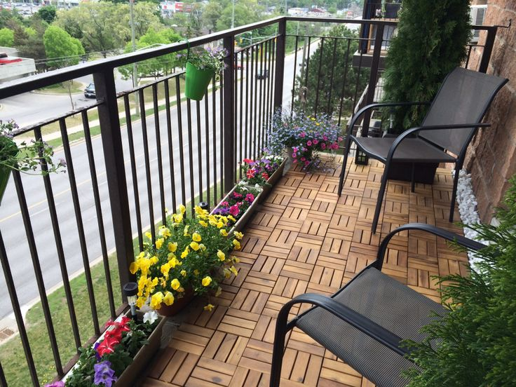 Turn a boring concrete apartment balcony into your own garden oasis. We bought wood tiles that snap together and sit on top of the concrete. It's not permanent so you can take these with you. Flower boxes from the dollar store and flowers from local greenhouse nursery. Two potted cedar trees are flanked on both sides of the seating area for additional privacy. White stones for filler and a nice zen feel. On other side (not shown in photo) there's a small BBQ and a small Ikea table.