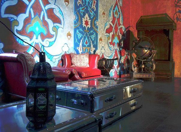 Дизайн мансарды загородного дома в подчеркнуто восточном стиле: синие стены, цветной орнамент, резная деревянная мебель и медные предметы декора.