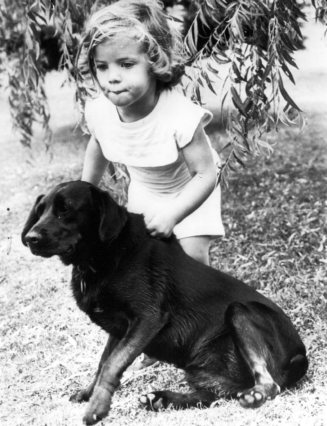 Caroline Kennedy, daughter of Democratic candidate for President John F. Kennedy, plays in with a neighbors dog in the driveway of their home, 1960.