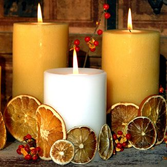 Create a citrus scented centerpiece by thinly slicing lemons and oranges, drying them in a 250 degree oven and then apply to thick pillar candles with hot glue. The warmth of the candles will release a gentle scent throughout the evening.