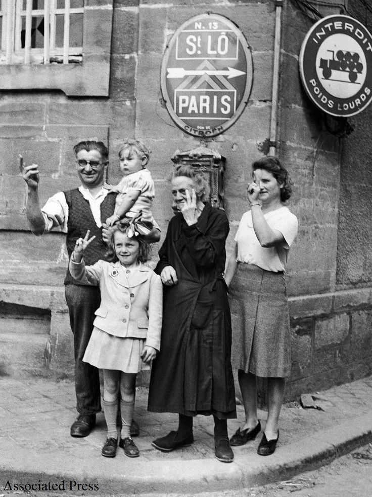 French civilians on the outskirts of St. Lo on July 25, 1944, cheer on allied troops with the V for victory signs.
