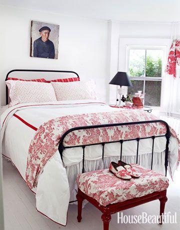 """consulente di design Ellen O'Neill mette in mostra il lato più dolce di rosso in un Bridgehampton, New York, casa.  """"E 'conveniente avere quattro camere da letto con lo stesso schema di colori"""", dice.  """"Quando si tratta di fogli, ho appena comprato niente con il rosso in esso. Quindi, tutto funziona in qualsiasi stanza.""""  Vintage biancheria rosso-controllato dal mercato delle pulci di Parigi riprende il tessuto rosso-controllato finestra-ombra da Ralph Lauren in una delle camere di questa…"""