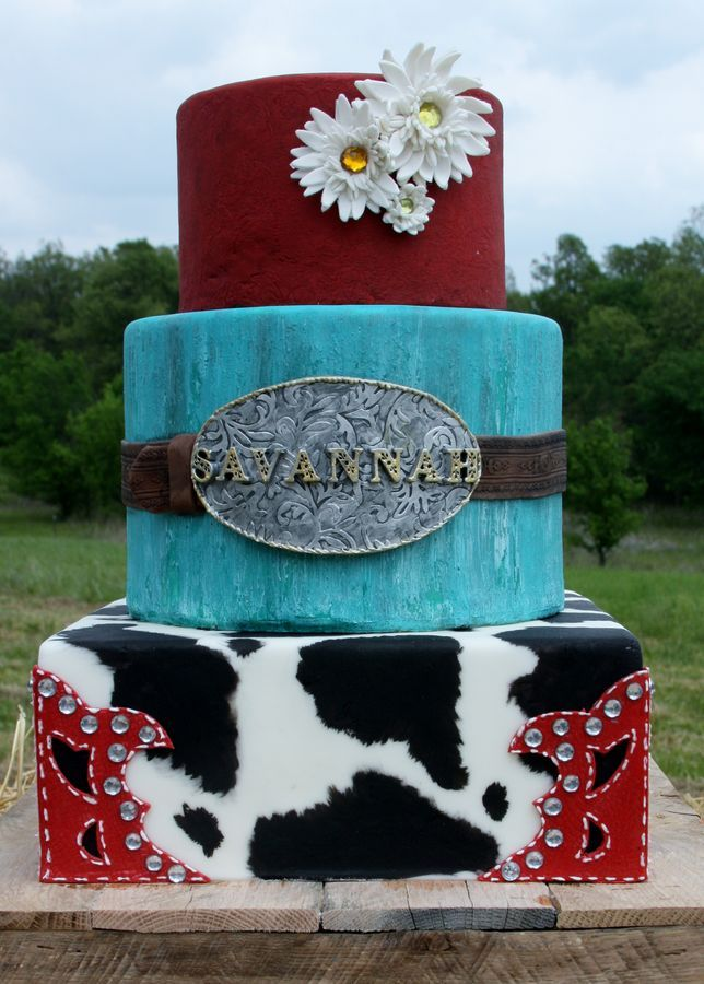 Bottom tier is hand painted cow print, red alligator skin fondant with bling. Middle tier is hand painted distressed wood look with fondant leather belt and gumpaste belt buckle. The top tier was supposed to look like imprinted leather, but it didn't show up as much as I had hoped it would. Gumpaste daisies with bling centers.