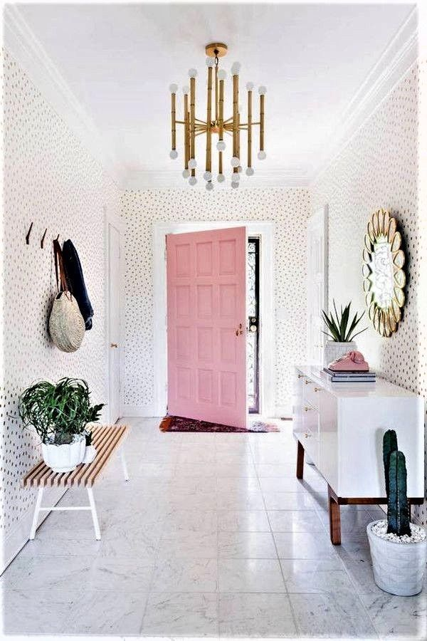 A bright and bold door pairs beautifully with brass accents and plants in this cheerful foyer.