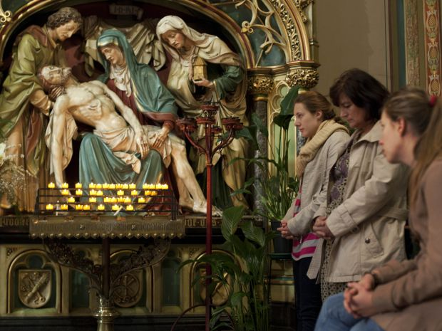 Three worshippers offer prayers during Good Friday Mass at Krijtberg church in Amsterdam on April 6, 2012. The Dutch Bureau for Tourism and Congresses expects some 850,000 tourist to visit the Netherlands over the Easter weekend.