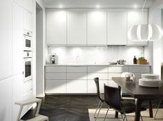 Hvidt køkken med hvide hvidevarer, sortbrune læderstole og spisebord.