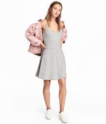 En kort klänning i mjuk, bomullsblandad trikå. Klänningen är v-ringad och har smala, reglerbara axelband. Avskuren i midjan med lätt utställd kjol.
