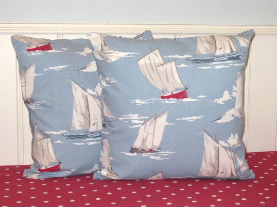 Two Nautical Cushion Covers featuring Sailing boats and Lighthouses in shades of pale blue with accents of red and white.  Each seaside themed pillow cover features the sailing boats fabric on the front and is backed with ta matching ticking stripe in the same shades of blue and