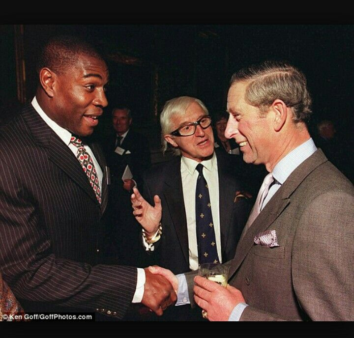 The black man, heavyweight boxer Frank Bruno, is the same guy photographed shaking hands with the Yorkshire Ripper, Peter Sutcliffe with Jimmy Savile looking on.  This is practically the same shot, but instead of the Yorkshire Ripper, it's Prince Charles.