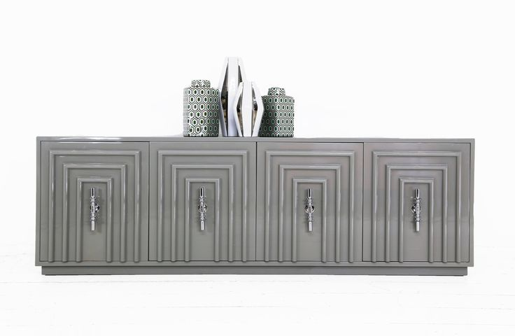 A modern twist on the classic art deco styling. Elegant and symmetrical, the Art Deco Credenza shows off its style and sophistication through it's four square trellis doors and its grey glossy finish.