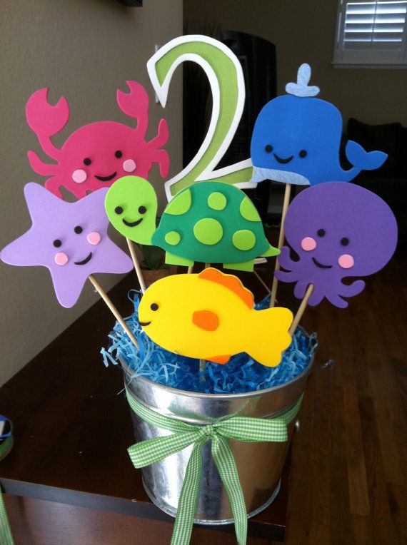 I did something like this for Hailey with Dora printables and tied balloons to a cut off bottom piece of plastic hanger, placed in vases and candle hurricanes surrounded by tissue to hold it upright. Turned out really cute!