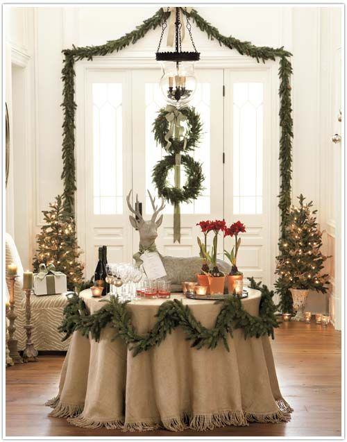 holiday style with greens and burlap and tiny white lights...I love the idea of garlanding the table.