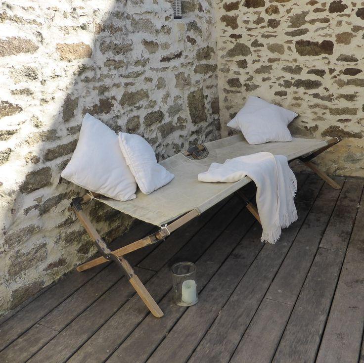 Ancien lit de camp militaire avec structure en bois poncée et ferronneries cirées en gris anthracite. La toile en coton est dans les tons beige / k...