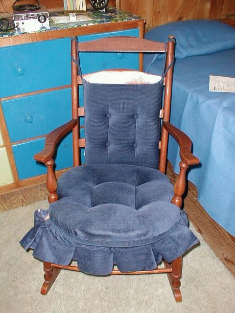 Archive photo: North Beach Camp bunk room: Wood Slat back rocker with arms; blue corduroy seat cushion, back cushion and skirt; woven fiber strap seat. Circa 1947. #1947, #atwoodhouse, #chatham, #northbeachcamp, #nickersoncamp, #capecod, #chathamhistoricalsociety, #antique, #rockingchair, #chair