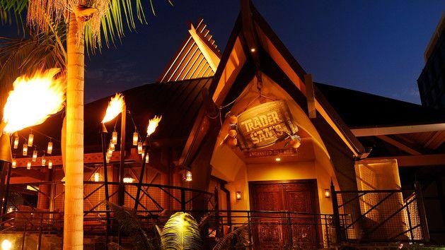 Lit tiki torches at night along the path to Trader Sam's Enchanted Tiki Bar at Disneyland Hotel