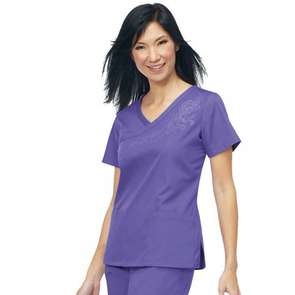 Orange Standard Malibu Top in Purple. This mock wrap ladies scrub top comes in a variety of fresh, bright colours. The Orange Standard Malibu Top has a stylish Y neckline with beautiful floral detail, side slits for easy fitting and two practical pockets. This scrub top looks fantastic with Orange Standard Laguna Trousers and is made from 65% Polyester and 35% cotton. £19.99  #nursescrubs #dentistuniform #nurses #dentists #purplescrubs