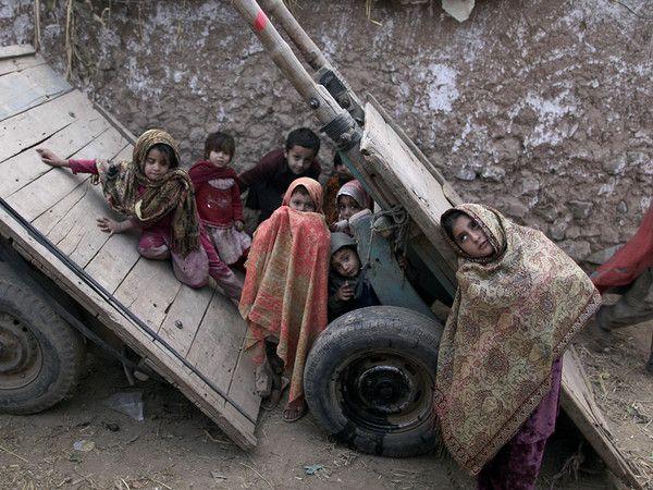 Niños Afganos refugiados juegan en el callejón de un barrio de las afueras de Afghan Islamabad, Pakistán. La foto es de Muhammed Muheisen.