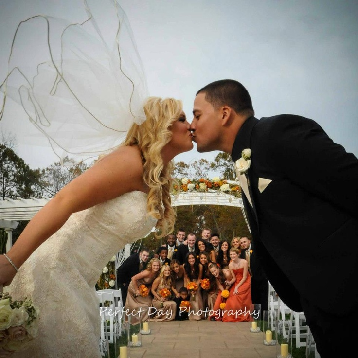 Bridal party peeking as the Bride and Groom share a kiss!  Such a great way to get a picture of the entire bridal party