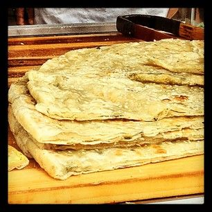 One is a thin rice flour bread with scallions and sesame seeds that is baked on a griddle, in a large pizza like circle and cut accordingly.  I have taken a page from that book to create a gluten and yeast free version of Jeffery Alford & Naomi Duguid's Oasis Naan.