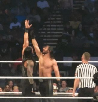 Roman Reigns making Seth Rollins reach.