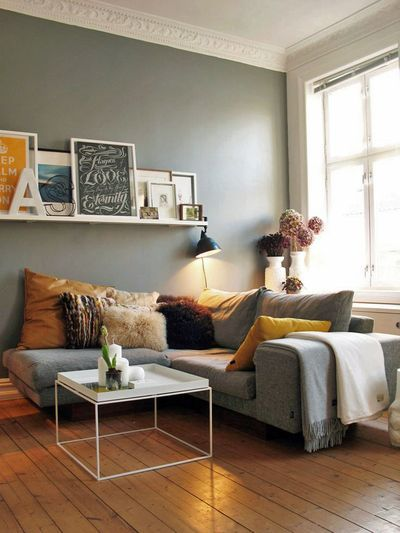 Floating shelf with art will fit behind a couch nicely and add some 3D