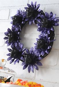 Are you in Halloween mode? Of course you are! This is a funky themed Halloween wreath that incorporates a little Dia de los Muertos flair (the flowers) with some plastic skulls and traditional Halloween...