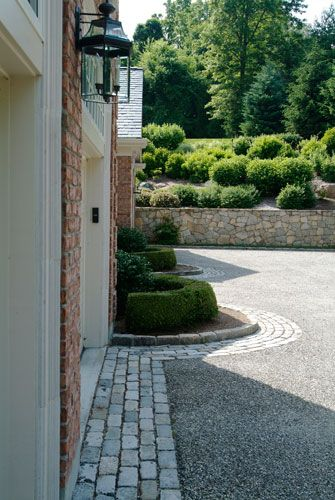 cobblestone border surrounding a pea gravel drive. nice threshold to the garage.