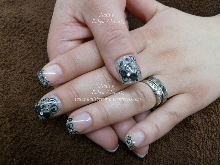 Gel nails, 3D gel bows, glitter, and hand painted swirls.