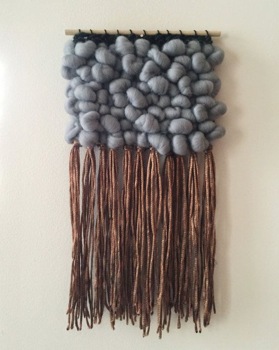 Handwoven wall hanging on a raw wooden dowel. Features a silvery blue grey texture of merino finished in silky copper fringe. Navy braid made of hand dyed yarn detail at top of weaving. Inspired by shifts in the seasons toward winter. Dimensions 7.5in x 13.5 in