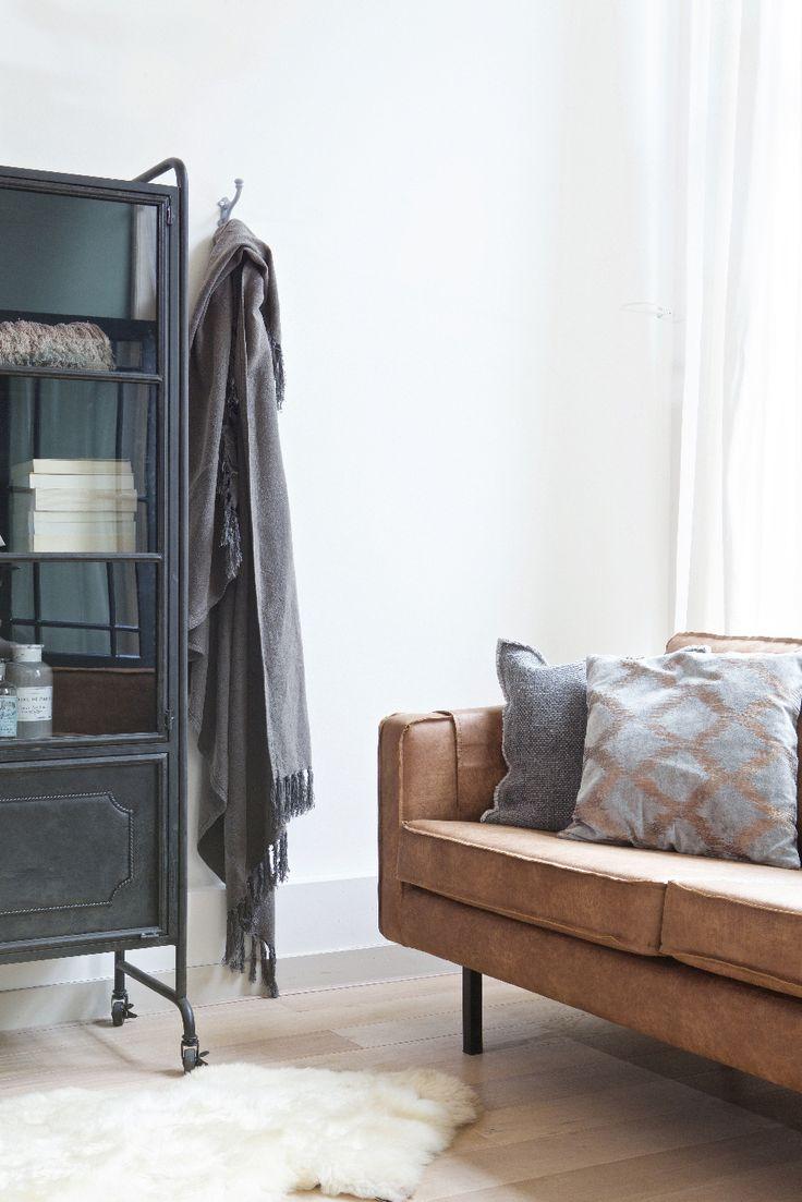 Zwarte metalen vitrinekast met een schapenvacht - bekijk en koop de producten van dit beeld op shopinstijl.nl