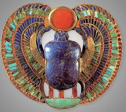 On this pectoral, the outer face is inlaid with colored glass and semi-precious stones, the reverse with chased decoration. The motif of the scarab pushing solar disc has been elaborated to form the king's prenomen, Nebkheprure.