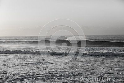 Ocean wave wall crashing along beach coastline vintage black and white.
