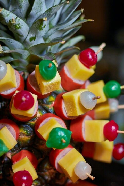Maybe a fresh pineapple with appetizers poking out? Ham/veg. ham, cheese, pineapple? Olives?
