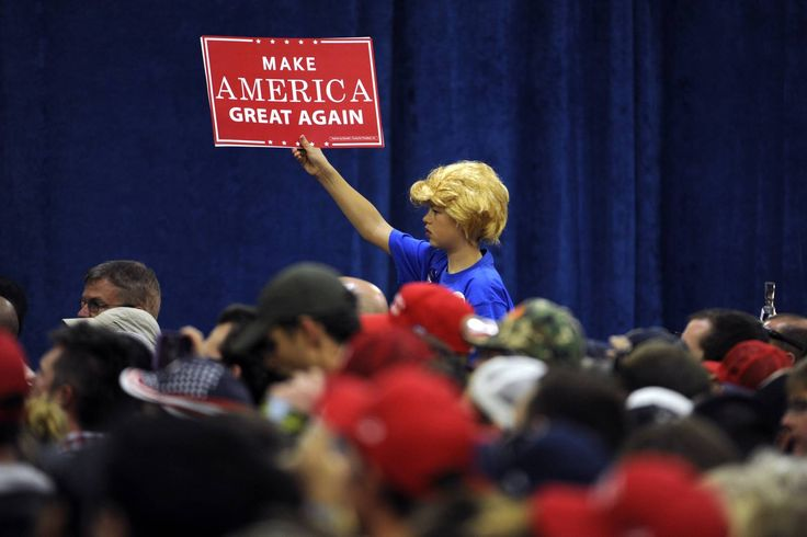 A young boy wearing a Donald Trump wig holds up a campaign sign during Republican presidential nominee Donald Trump's campaign rally at the Bank of Colorado Arena on the campus of University of Northern Colorado in Greeley, Colorado on October 30, 2016.