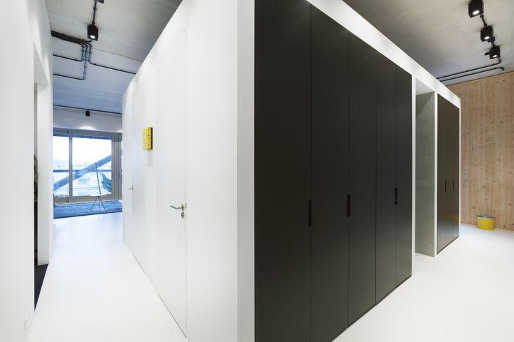 Een strakke inloopkast gecombineerd met een doorgang. De zwart deuren gecombineerd met de licht gietvloer en houten wanden zorgen voor een strakke en warme uitstraling. Ontwerp BNLA architecten | Fotografie Wim Hanenberg
