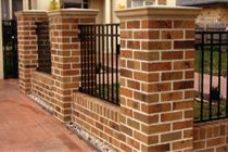 Brick and iron fence with grey cap stone