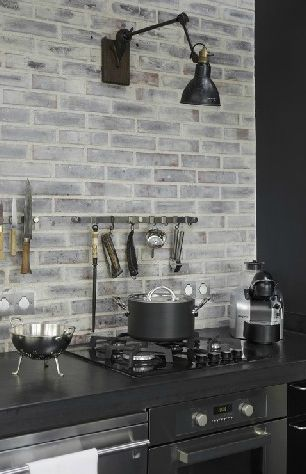 Gray brick in place of a backsplash to contrast the black countertops make for a classic streamlined look.