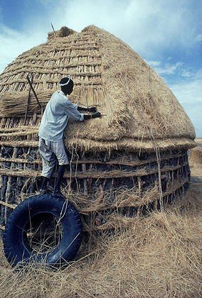 Africa | Dinka man stands on an old truck tire while thatching his hut near Malakal in southern Sudan. ©Robert Caputo