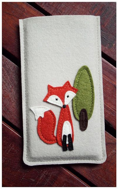A felted phone case with a sewn fox.