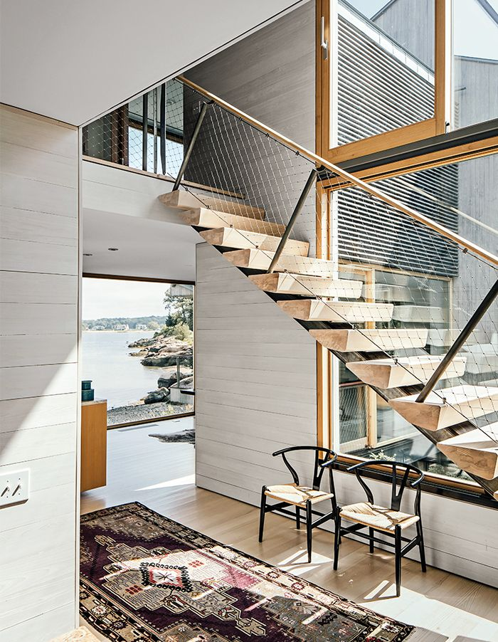 The white cedar board paneling in the interiors mimics the exterior; the ones inside are bleached for a lighter finish. Fixed glass picture windows are by Town & Country Glass. Unalam and JIG Design Build fabricated the staircase with ash risers on a single stringer, a Gray Organschi hallmark.