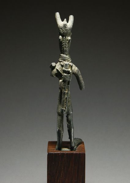 SARDINIAN BRONZE STANDING WARRIOR Wearing a horned helmet and a short V-neck tunic, with a high layered collar, with a quiver hanging down ...