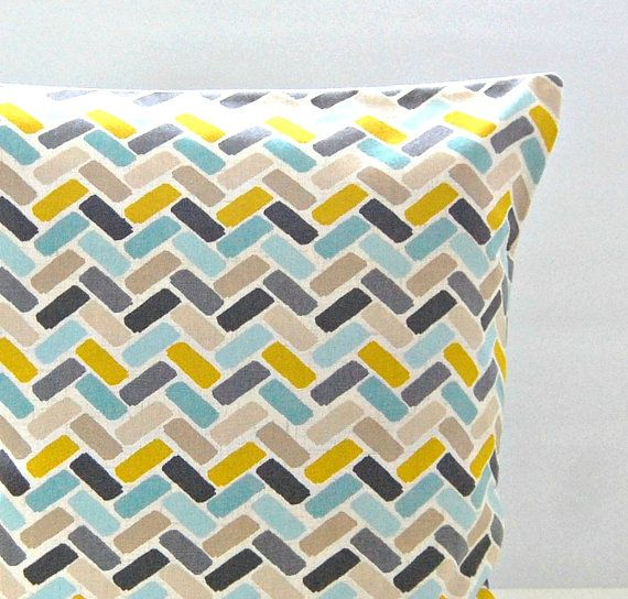 This 16 inch (40 cm) cushion cover has blue, yellow, mustard, grey and charcoal grey oblong blocks on a light beige lined background.  Fabric is