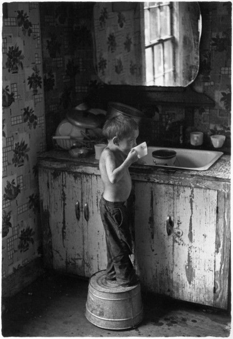 .look at that wallpaper, drainer full of dishes, the sink....and that sweet little boy..........